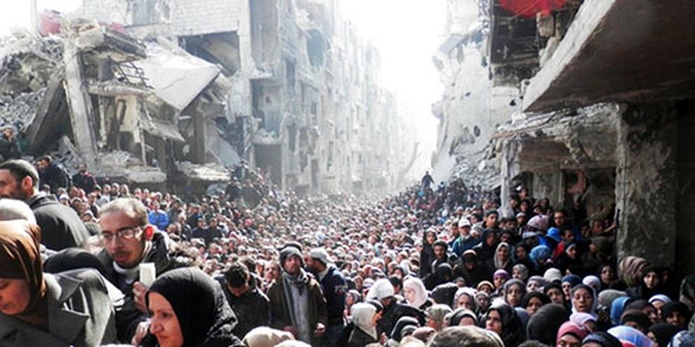 Les habitants de Yarmouk attendent de recevoir de la nourriture distribuée par l'Office de secours et de travaux des Nations unies. © unrwa.org