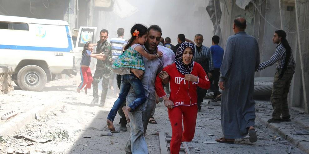 Une famille fuit les décombres d'un batiment visé par les frappes aériennes dans le quartier de Al-Qatarji au Nord d'Alep occupé par les rebelles, 29 avril 2016. © AFP / Getty Images