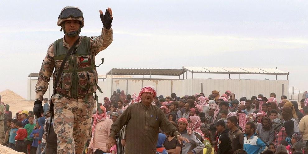 Un soldat jordanien monte la garde tandis que des réfugiés syriens tentent de rejoindre Ruwaished au nord-est de la frontière jordano-syrienne. © KHALIL MAZRAAWI/AFP/Getty Images