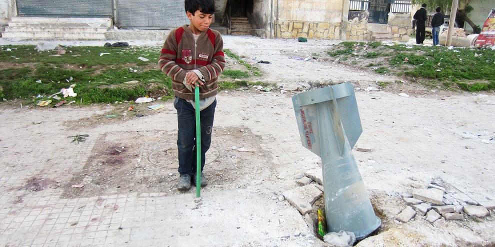Un enfant regarde une bombe à sous-munitions larguée à Alep, en 2013. Des armes de ce type sont utilisées également dans des bombardements touchant la population civile en Ghouta orientale. © Amnesty International