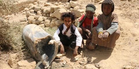 Des enfants dans la ville de Saada au Yémen assis à côté d'un obus. © Amnesty International