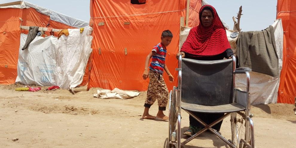 Sur cette photo prise au camp de Mishqafa, Lahj, le 11 juin 2019, Lola Ahmed, la mère d'une jeune fille de 16 ans ayant une déficience physique et intellectuelle, lutte pour pousser un fauteuil roulant donné à sa fille. © Amnesty International