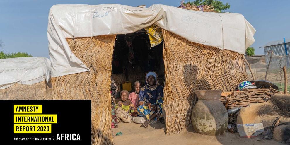 Falmata, âgée d'une soixantaine d'années, est assise dans son abri avec deux de ses petits-enfants, dans un camp de personnes déplacées de l'État de Borno, dans le nord-est du Nigeria, en octobre 2020. © The Walking Paradox / Amnesty International