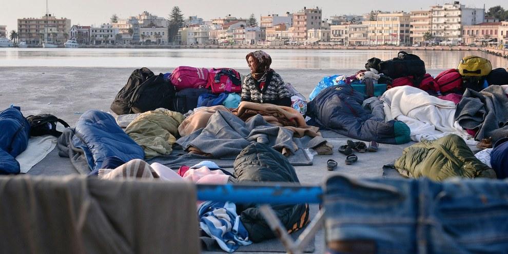 Une femme réfugiée se réveille dans le port de Chios, où les réfugié·e·s et les migrant·e·s passent leur nuit à l'air libre. 5 avril 2016.