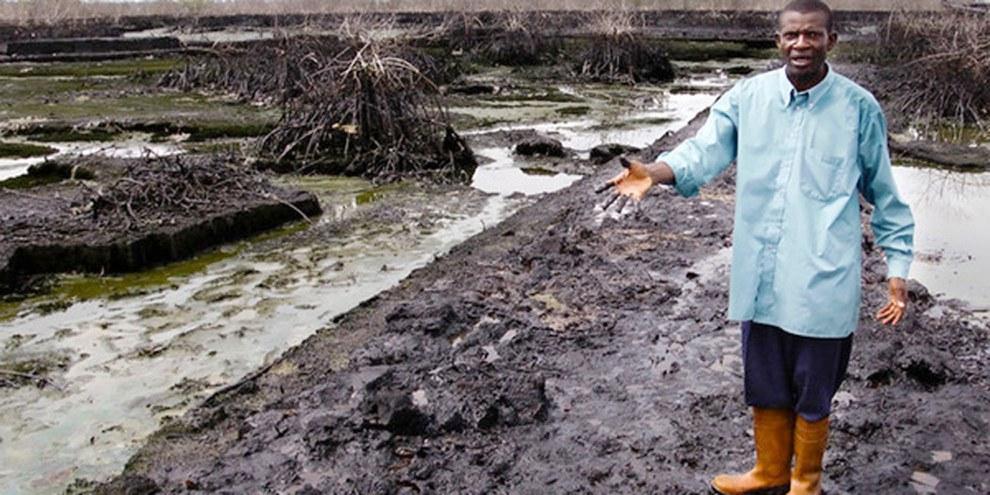 Christian Lekoya Kpandei montre son champ détruit par une fuite de pétrole de l'entreprise Shell. © Amnesty International