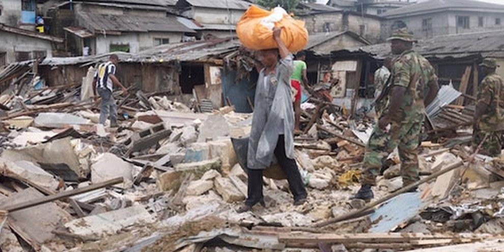 Un homme porte ce qu'il a pu sauver de chez lui après la démolition de son logement. Quartier d'Abonnema Wharf, 27 juin 2012. © DR