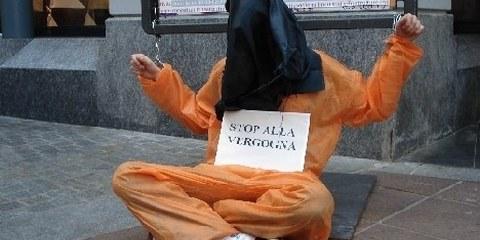 Un militante incappucciato e ammanetato durante la manifestazione