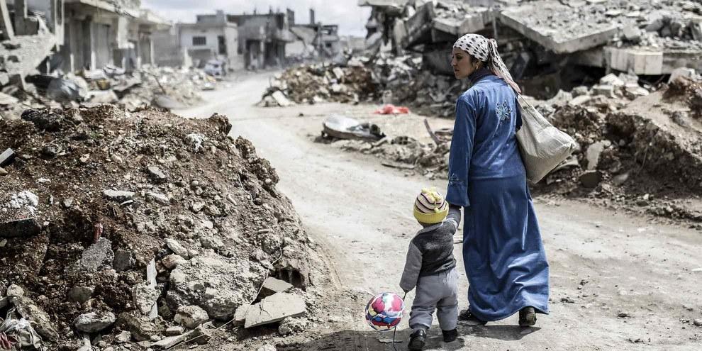 Una donna curda cammina tra le macerie nella città di Kobane, conosciuta anche come Ain al-Arab, nel marzo 2015. © Yasin Akgul/AFP/Getty Images