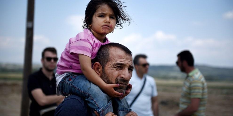 In Grecia, un siriano e sua figlia lasciano il campo di Indomeni dopo un'operazione di evacuazione della polizia greca. ©Shutterstock
