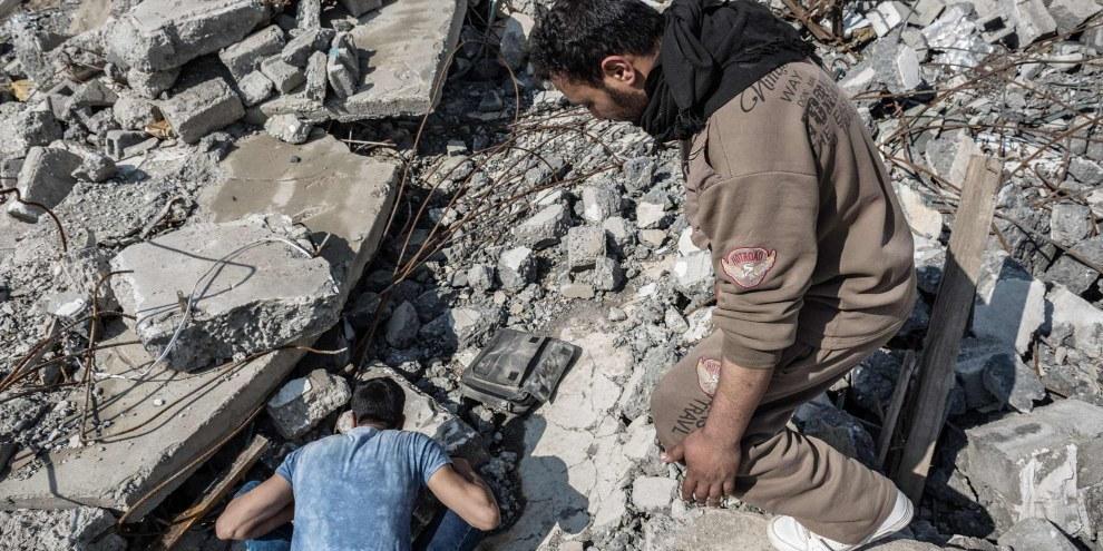Con l'aiuto di un amico, un sopravvissuto fruga tra le macerie della sua casa, distrutta da un raid aereo del 14 marzo, che ha colpito il quartiere al-Sekar a Mosul est. © Andrea DiCenzo/Amnesty International