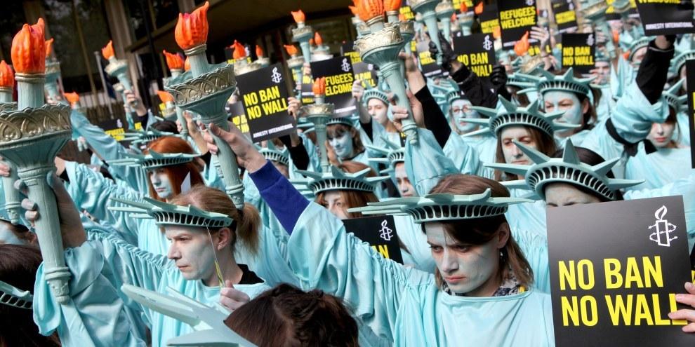Un centinaio di statue della libertà hanno sfilato davanti all'Ambasciata statunitense a Londra, il 27 aprile 2017, per segnare i primi 100 giorni della presidenza Trump. © Marie-Anne Ventoura/Amnesty UK