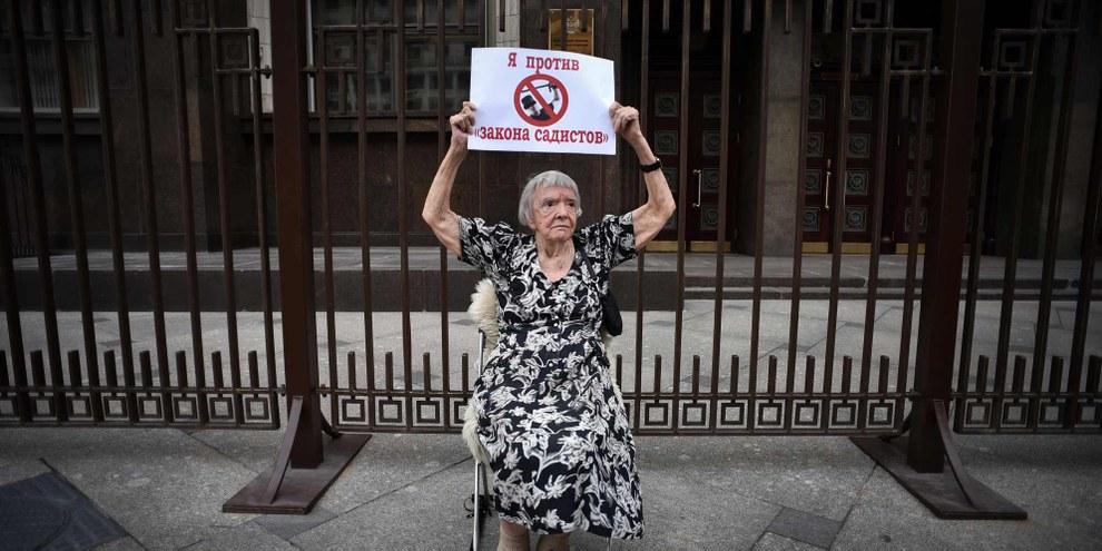 """Ludmila Alekseyeva, presidente del gruppo Mosca Helsinki e membro del Consiglio dei diritti dell'Uomo del Cremlino, con un cartello che dice """"Mi oppongo alle vostre leggi sadiche"""", Maggio 2015 © AFP/Getty Images"""