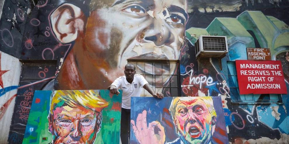 L'artista kenyota 'Yegonizer' posa con i suoi ritratti di Trump davanti a un murales dedicato a Obama dell'artista Bankslave. © Keystone/EPA/DAI KUROKAWA