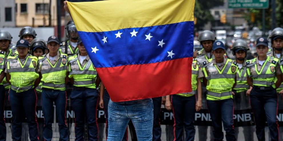 Un sostenitore dell'opposizione sventola la bandiera nazionale davanti a dei poliziotti durante una manifestazione a Caracas, luglio 2016.© Juan Barreto/AFP/Getty Images