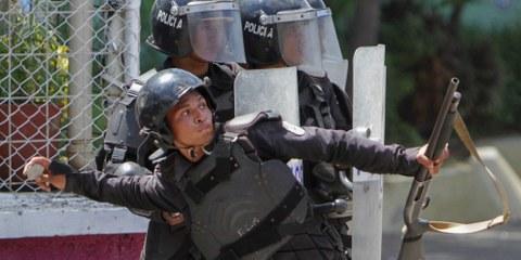Managua, 19 aprile 2018 : un poliziotto lancia una pietra contro gli studenti che protestano davanti all'Università. © Inti Ocon/AFP/Getty Images