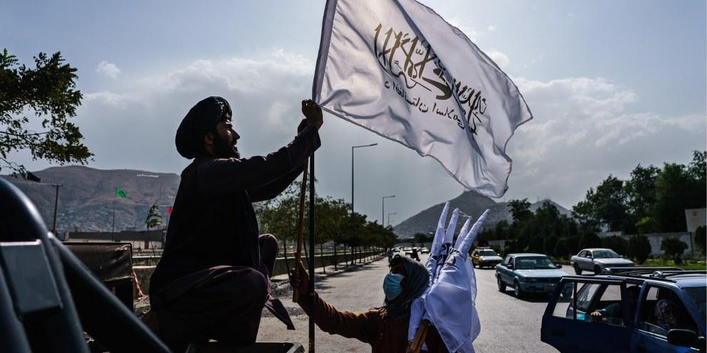 Il mollah Esmatullah Khadir sventola una bandiera talebana dopo la caduta di Kabul, il 20 agosto 2021 © Marcus Yam / Los Angeles Times